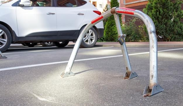 Ручной парковочный барьер из оцинкованного металла серого цвета с замком. устройство блокировки парковки. установлен парковочный барьер. складной барьер предотвращает остановку автомобиля в этом месте. зарезервированное место.
