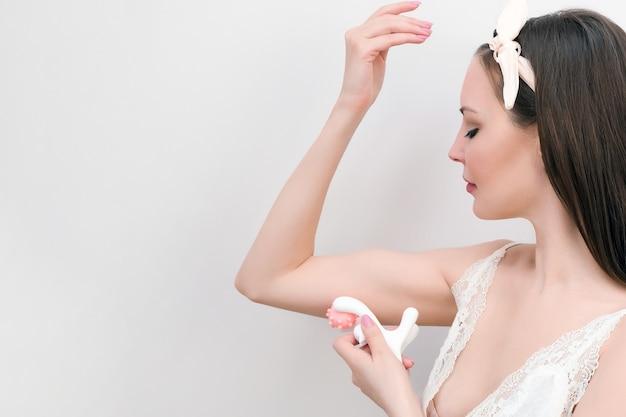 수동 마사지기. 아름 다운 젊은 여자는 자신을 손 마사지를 만든다. 자연 색상