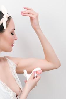 Ручной массажер. красивая молодая женщина делает себе массаж рук. естественные цвета