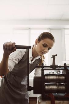 수동 작업 방법. 작업장에서 압연 기계로 금속을 만드는 젊은 여성 금세공인의 초상화. 주얼리 제작 과정. 사업. 보석 작업실.