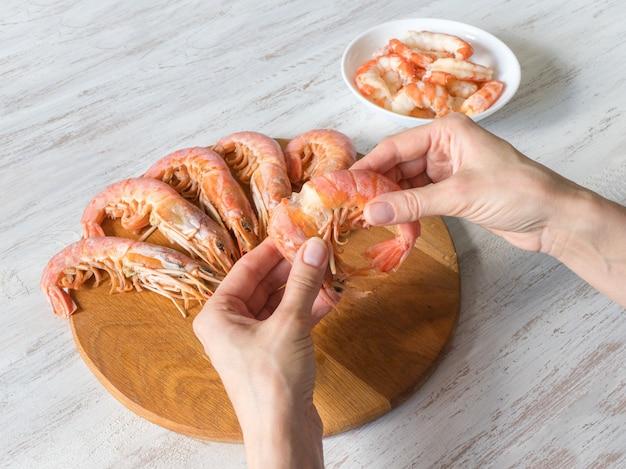 エビの手による皮むき。調理した新鮮な巨大なエビ、クローズアップ