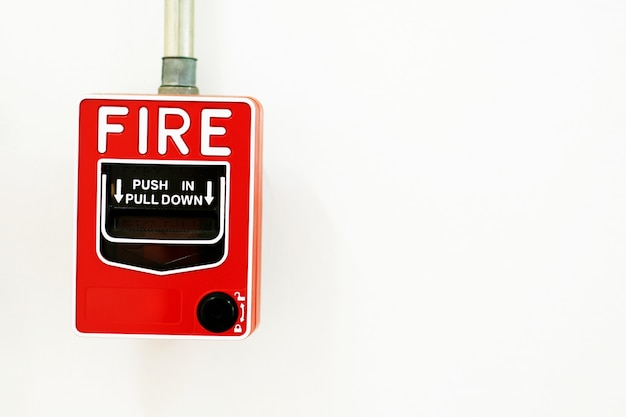 Manual pull fire alarm switch installed on white wall.