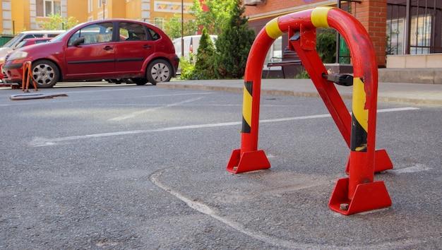 Ручной металлический парковочный барьер красного цвета с замком. устройство блокировки парковки. установлен парковочный барьер. складной барьер предотвращает остановку автомобиля в этом месте. зарезервированное место.