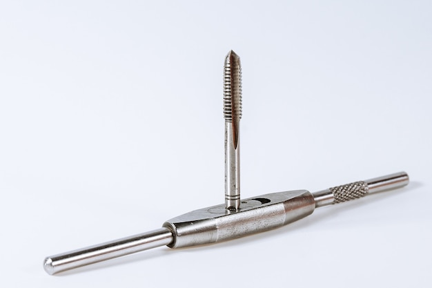 Manual tap for cutting threads in metal on a white background. metal processing tool. copy space.