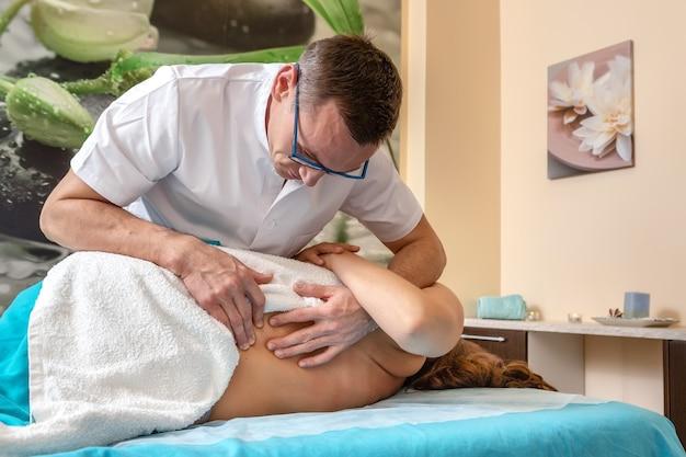Мануальный терапевт остеопат производит манипуляции с пациентом.