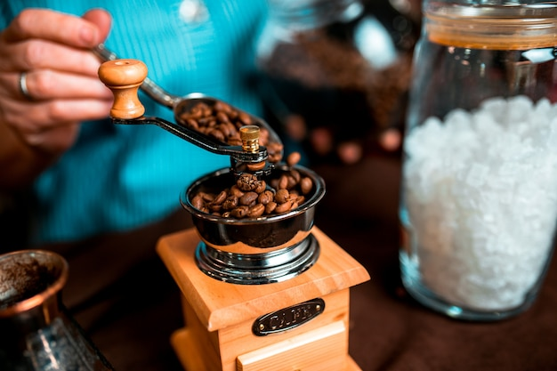 Manual wooden coffee-grinder with coffee beans inside.