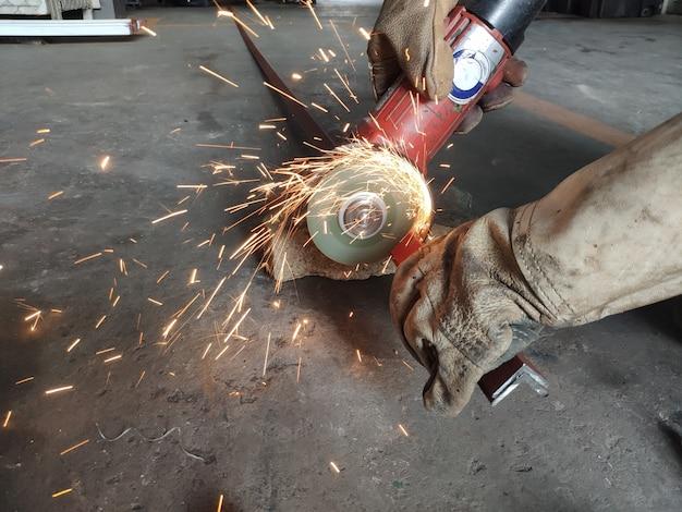 Manual worker cutting metal.