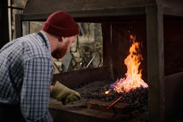 Рабочий в защитных перчатках добавляет угли, чтобы сжечь пламя в печи