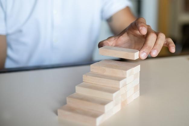 木のブロックの積み重ねを階段状の階段として手動で整理します。ビジネスの成長プロセスの成功の概念