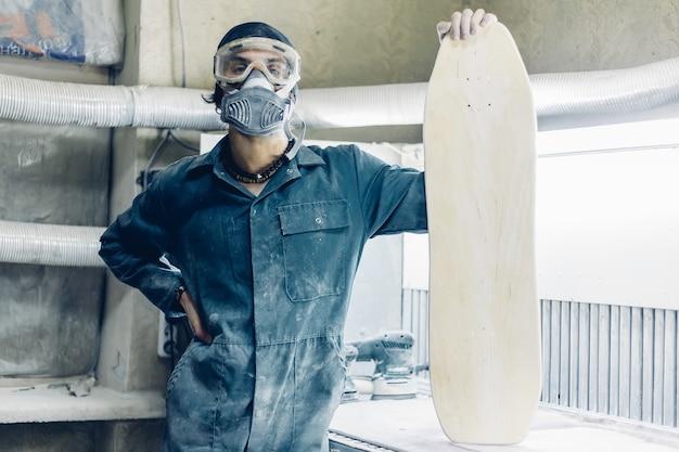 Производство скейтбордов. у него есть защитная одежда и маска.