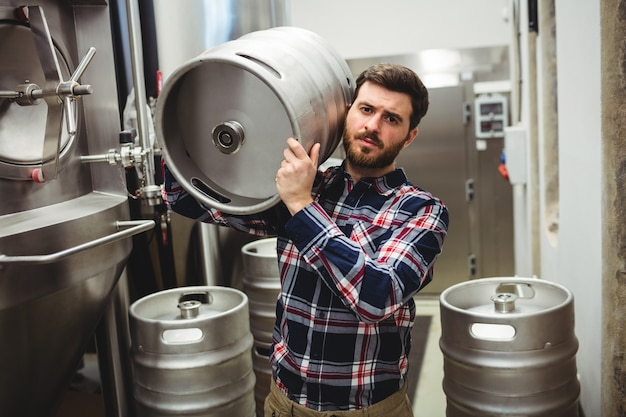 Manufacturer carrying keg in brewery