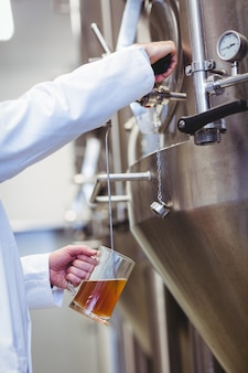 Manufacturer filling beer into glass at brewery