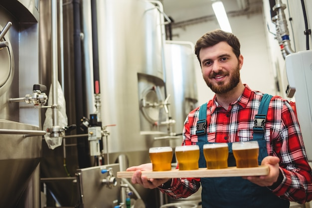 Manufacturer holding beer glasses in brewery