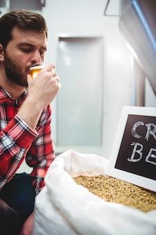 Manufacturer tasting beer at brewery