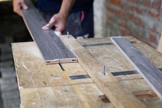 ドアの製造と設置。大工が旋盤で木の板を切る。