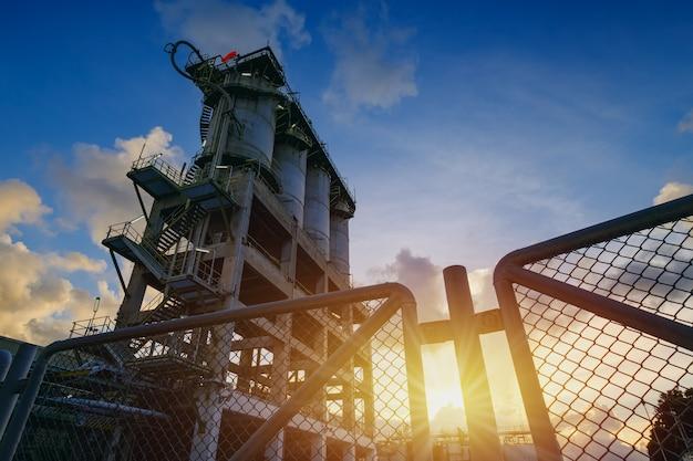 Производство нефтехимического промышленного завода с силосом для хранения на закате