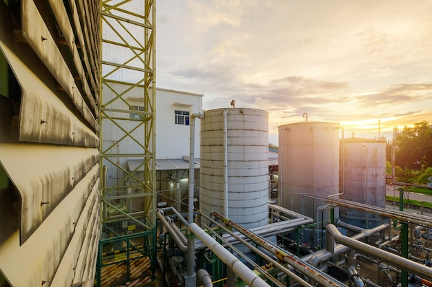 Manufacturing of petrochemical plant with storage tank on sunset sky