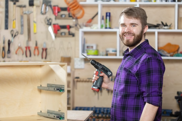 제조, 중소기업 및 작업자 개념 - 가구 공장에서 일하는 남자.