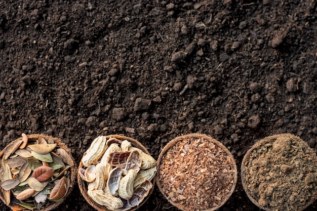 Manure, sawdust, dry leaves, peanut shells placed on a loamy ground.