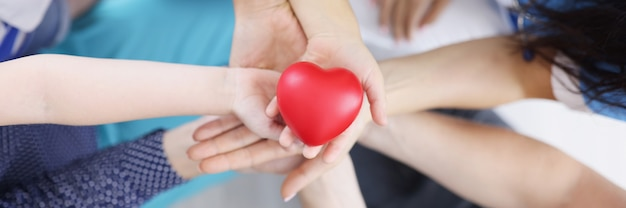 Многие взрослые и дети держат в руках пластиковую игрушку в виде сердца