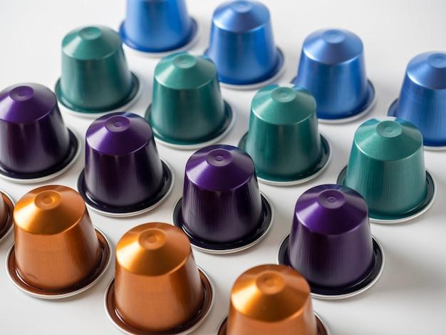 多くのアルミコーヒーカプセルが白い背景に一列に表示されます。フードパターン。コーヒーマシン用カプセル