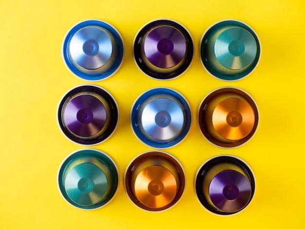 多くのアルミコーヒーカプセルが黄色の背景に一列に表示されます。フードパターン。コーヒーマシン用のカプセル。上面図、フラットレイ