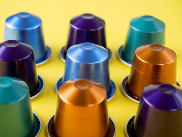 多くのアルミコーヒーカプセルが黄色の背景に一列に表示されます。フードパターン。コーヒーマシン用カプセル
