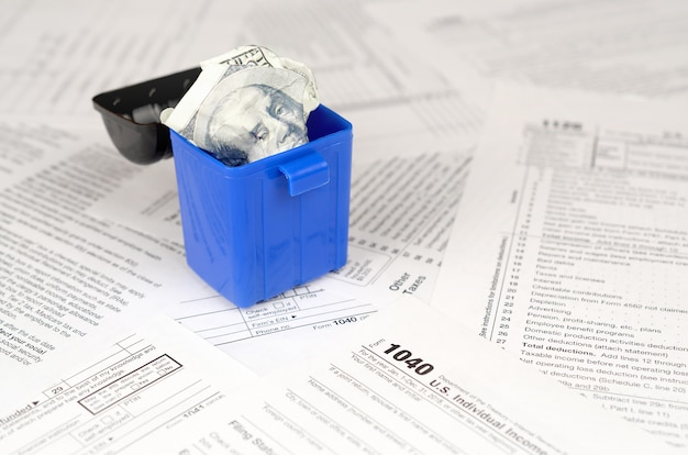 Many american tax blank forms and crumpled hundred dollar bill in trash bin