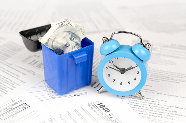 Many american tax blank forms with blue alarm clock and crumpled hundred dollar bill in trash bin