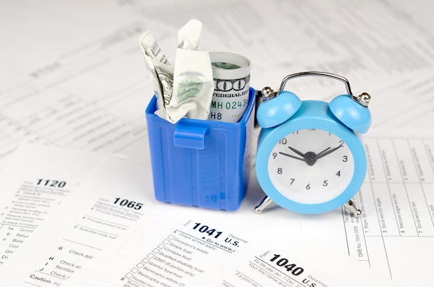Many american tax blank forms with blue alarm clock a