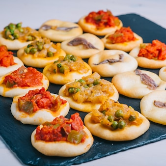 Many baked mini pizzas. traditional spanish pastry with vegetables.