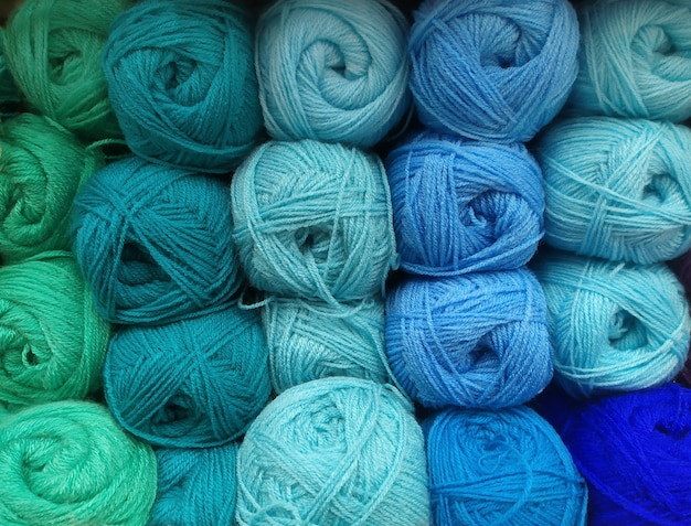 Many balls of wool yarn in natural shades of green and blue for knitting, crocheting. textured background