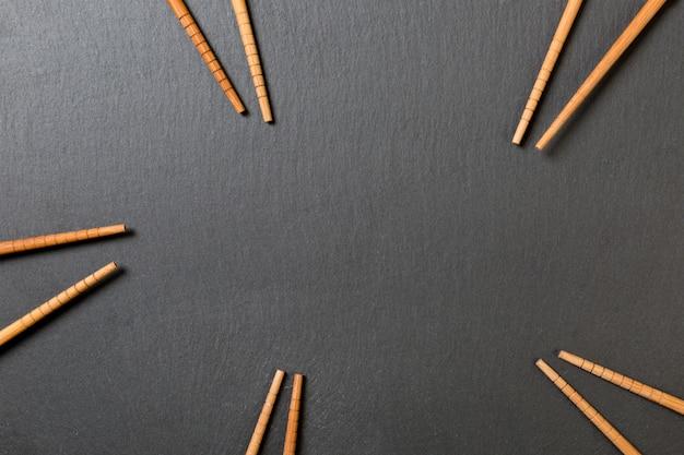 Many bamboo chopsticks on black slate