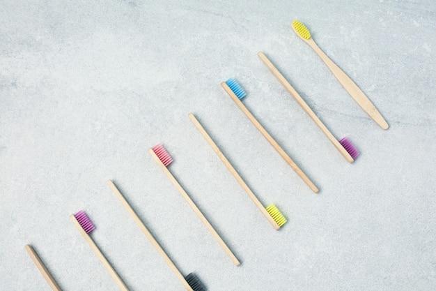 Многие бамбуковые зубные щетки на светлом каменном столе