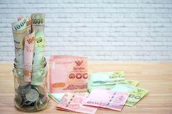 多くの紙幣と硬貨の木製テーブルの上のガラスの瓶