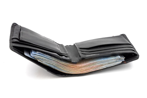 Many banknotes in black wallet on white background