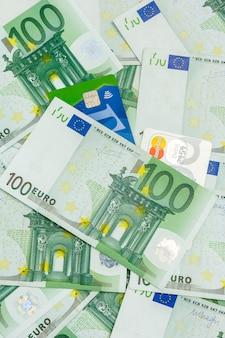 多くの100ユーロ紙幣と2枚のクレジットカードとデビットカード、ヨーロッパ通貨の山