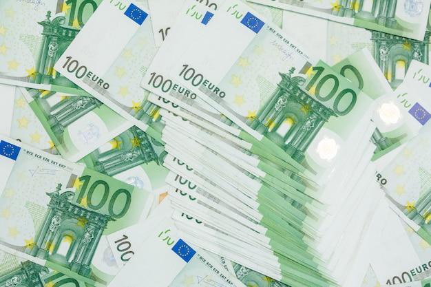 100ユーロの多くの紙幣、ヨーロッパの通貨の山