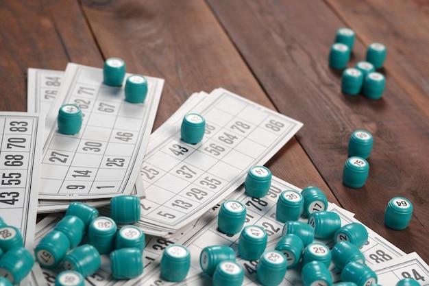 나무 표면에 로또 또는 러시아 빙고 테이블 게임을위한 숫자와 카드가있는 많은 배럴. 러시아 로또는 고전적인 전세계 빙고 게임과 유사한 규칙을 가지고 있습니다.