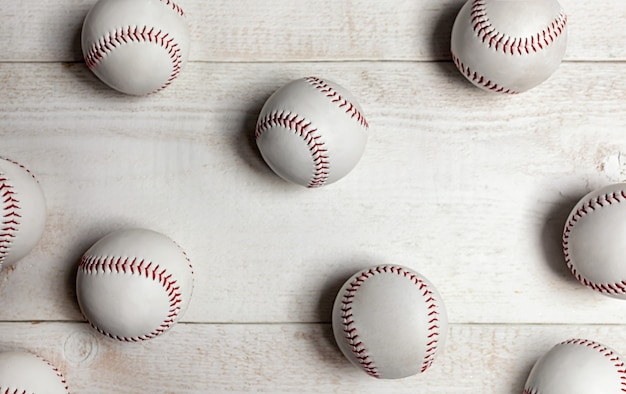 Many baseball balls on white wood