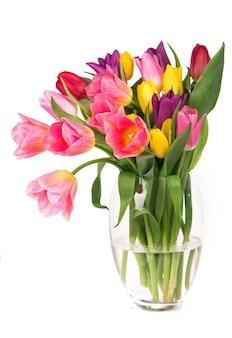 透明な背景に分離されたガラスの花瓶の葉を持つ多くの美しいカラフルなチューリップ。お祝いのデザインのための新鮮な春の花の写真