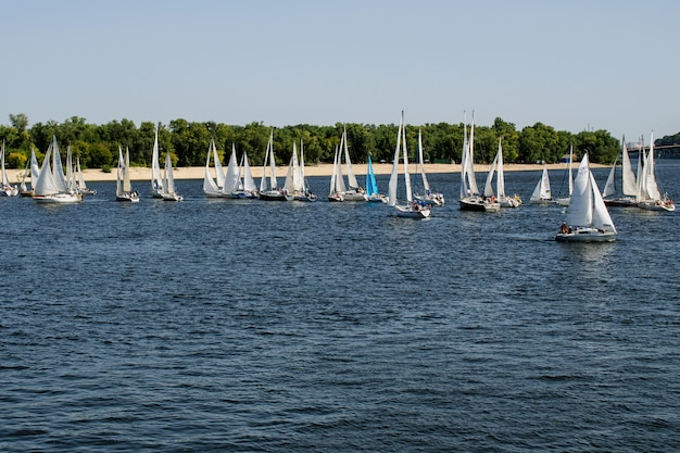 Many beautiful floating sail yachts medium size with crew, on dnieper river.