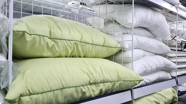 多くの美しい緑と白の枕が店の棚で売られています。