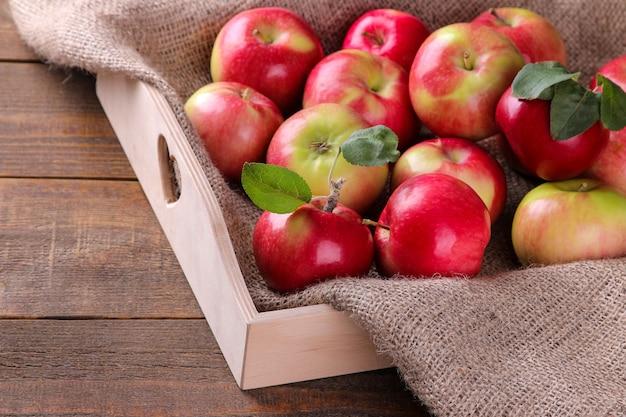 푸른 나무 탁자 위의 쟁반에 있는 많은 아름다운 익은 신선한 사과