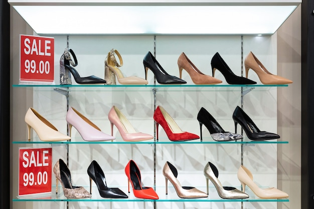 Many beautiful women's pumps stand on the window with a big sale