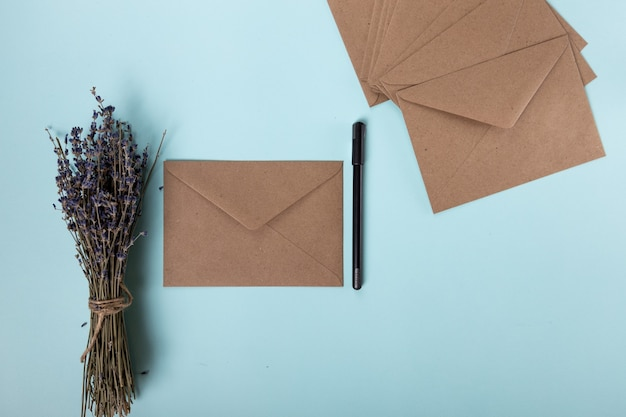 Many beige envelopes a black handle and dried lavender are beautifully laid out in a delicate blue b...