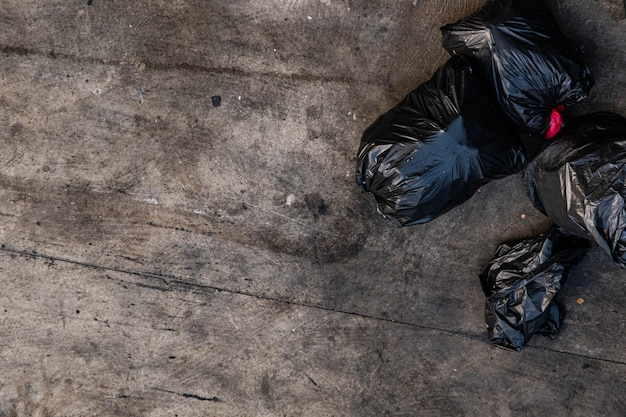 Many black garbage bags that are tied up on the sidewalk
