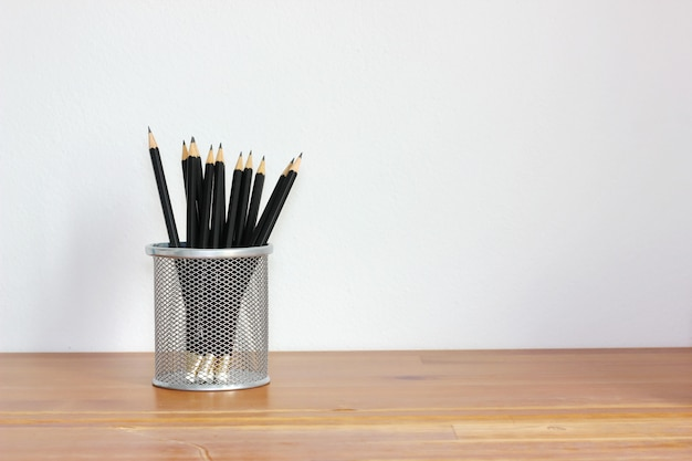 Many black pencils in basket  on wood desk or table with white wall,copy space.