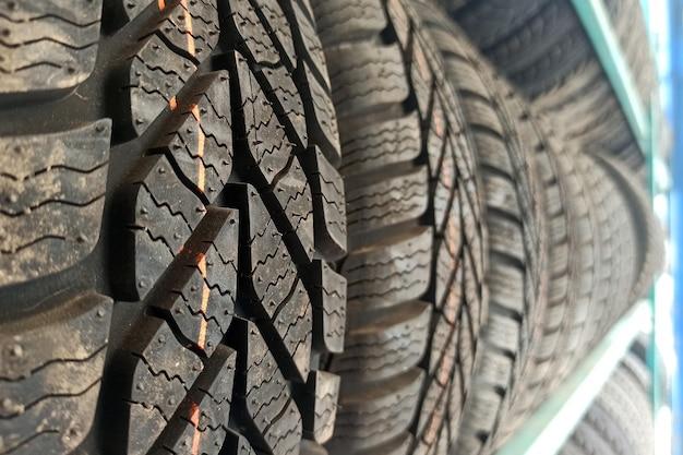 Многие черные резиновые автомобильные шины на полке магазина выставлены на продажу.