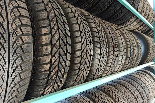 販売のための店の棚にある多くの黒いゴム製の車のタイヤ。